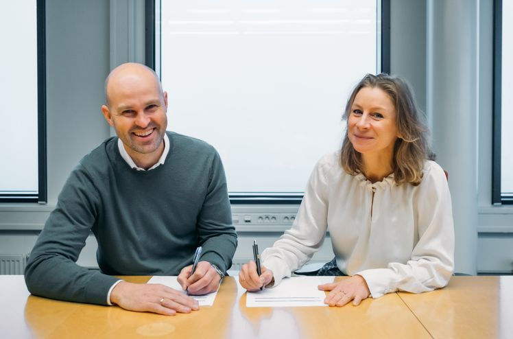 Styreleder Anders Kvåle i Spacemaker og konserndirektør Ida Aall Gram i AF Gruppen signerer avtalen om langsiktig samarbeid.