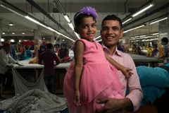 "Jamal Hossain, 26, a cutter at the Northern Tosrifa Group garment factory, poses for a portrait with his daughter, Jui, 30 months, in Gazipur, outside Dhaka, Bangladesh on 6 December 2018. The knowledge and awareness of parents about child care and care in Bangladesh is limited, including the way a child experiences the primary stage of life and how it plays a major role in creating a prosperous future. However, thanks to an in-factory day care centre provided by the Northern Tosrifa Group — and supported by UNICEF through partner organization Phulki — Jui is cared for throughout her parents' workday. ""We make about 20,000 taka (USD 238) between us per month. Paying for child care would cost at least 5,000 taka (USD 60), which is the difference between being able to save for the future, and not,"" Jamal says of his family, which includes his wife, Shumi Akhter, who also works at the factory. Photo: UNICEF UN0292143 / Brian Sokol"