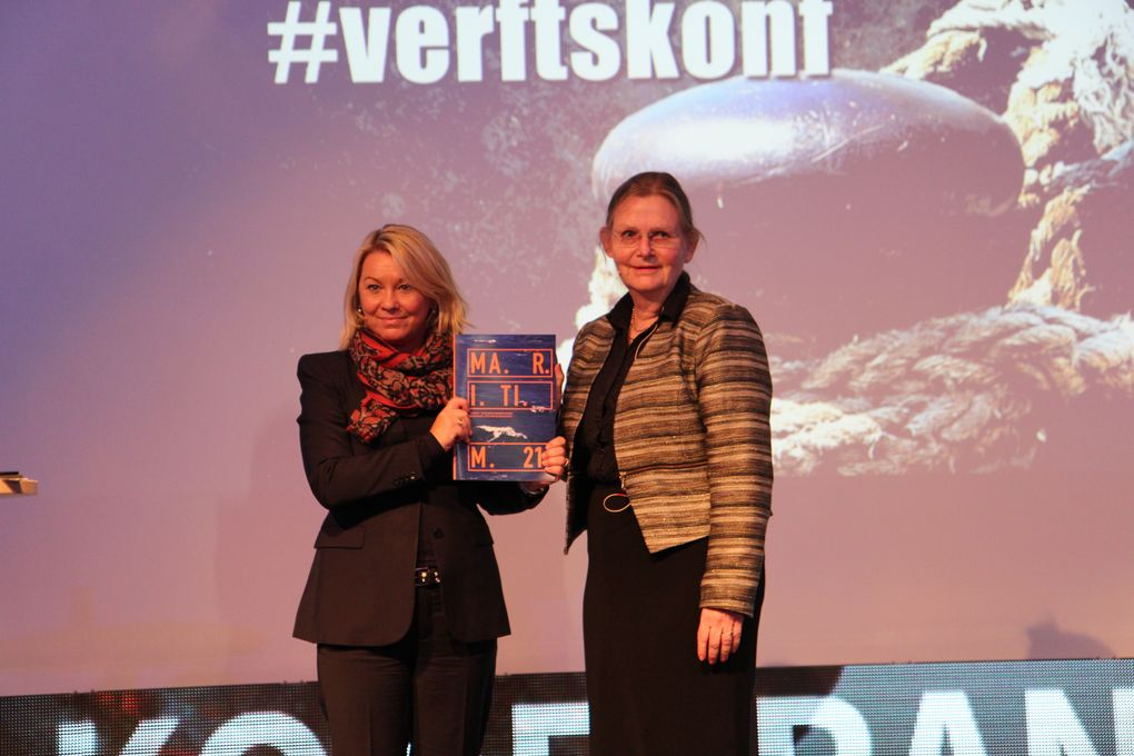 Leder av strategigruppa, Siri Pettersen Strandenes (til høyre), overleverer Maritim21-strategien til næringsminister Monica Mæland under åpningen av Verftskonferansen i Ålesund
