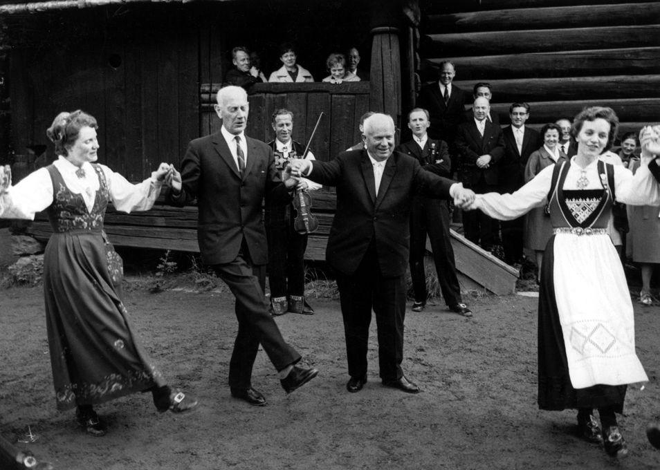 Sovjets leder Nikita Khrustsjov (til høyre) lærer å danse norsk folkedans under et statsbesøk i 1964 på Norsk folkemuseum på Bygdøy i Oslo. Her danser han sammen med Einar Gerhardsen. Foto: Erik Thorberg / NTB